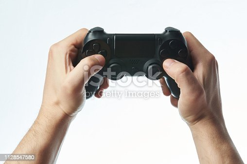 Holding game joystick in hands isolated on white background