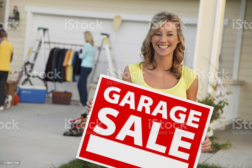 Holding Garage Sale Sign royalty-free stock photo