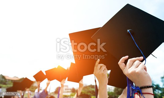Group of graduate students holding their graduation hats.
