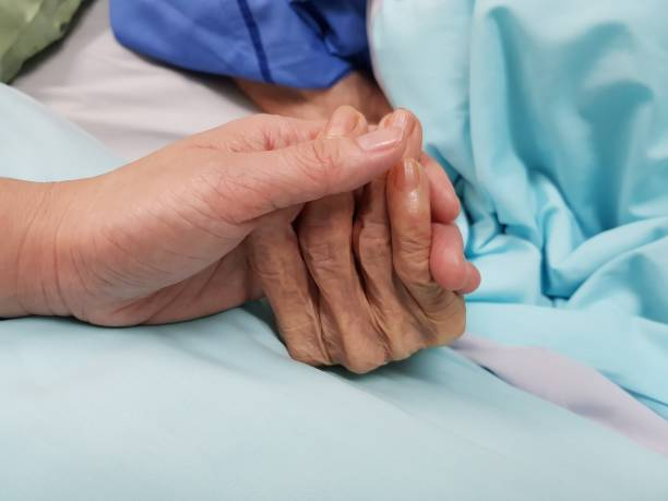 Holding grandmother's hand in the nursing care. Showing all love, empathy, helping and encouragement : healthcare in end of life and palliative concept stock photo