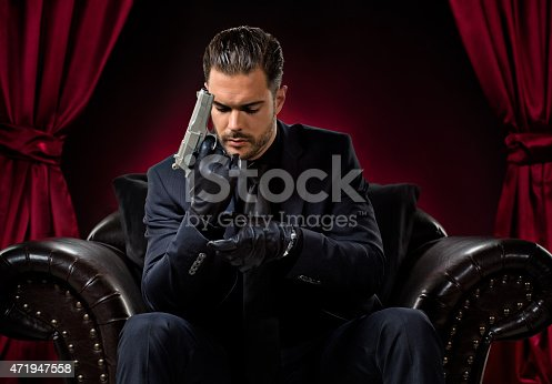 471947536 istock photo holding gun gangster sitting in chair 471947558