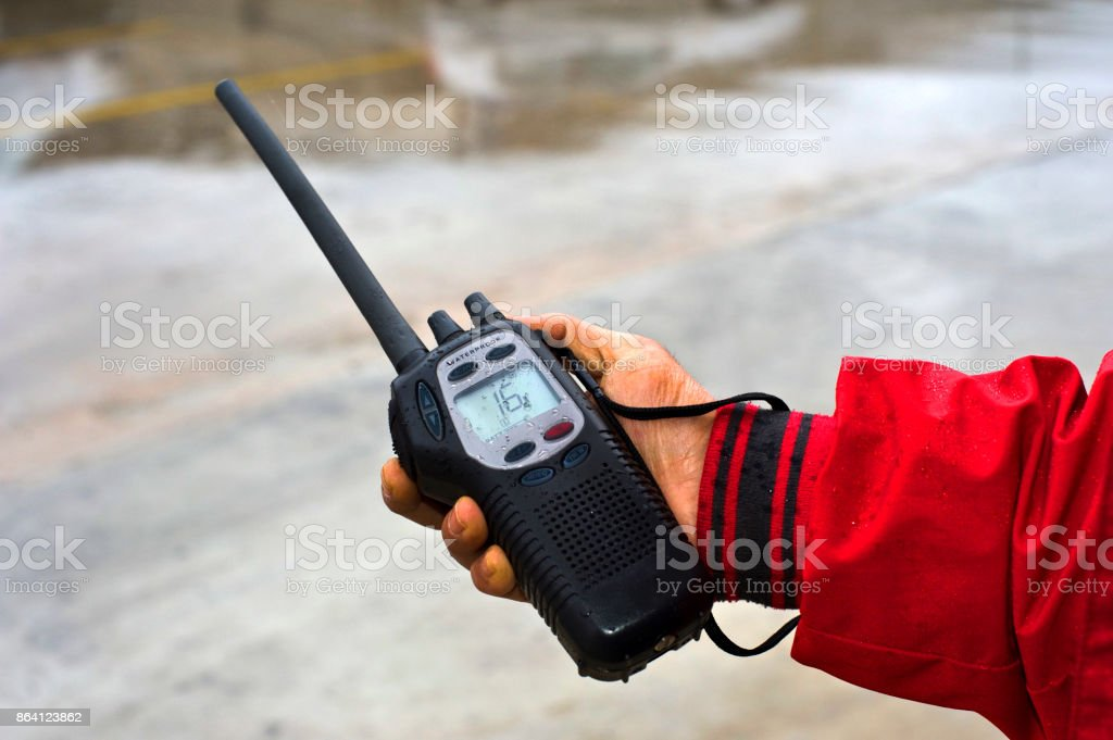 Holding handheld marine VHF Radio under the rain royalty-free stock photo