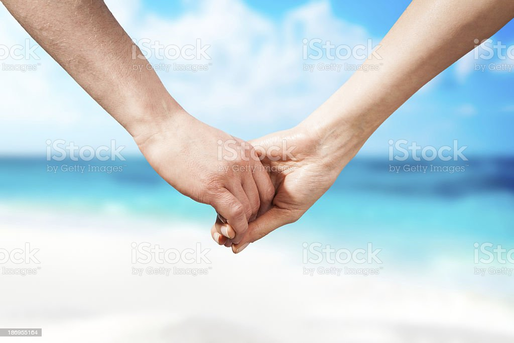 Holding hands couple on beach royalty-free stock photo