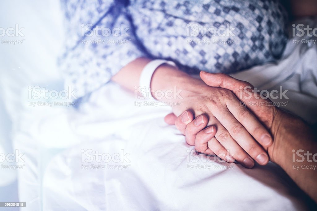 Holding Hands in Hospital Bed stock photo
