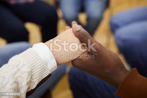 847516586 istock photo Holding Hands in Support Group Close up 1182683203