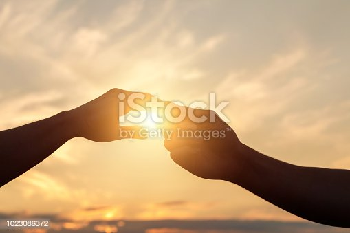 974882202istockphoto Holding Hands in the background of the sun. 1023086372