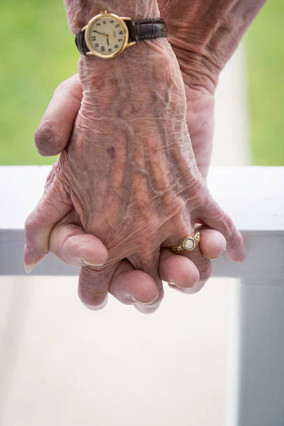 Holding Hands of an Elderly Couple stock photo
