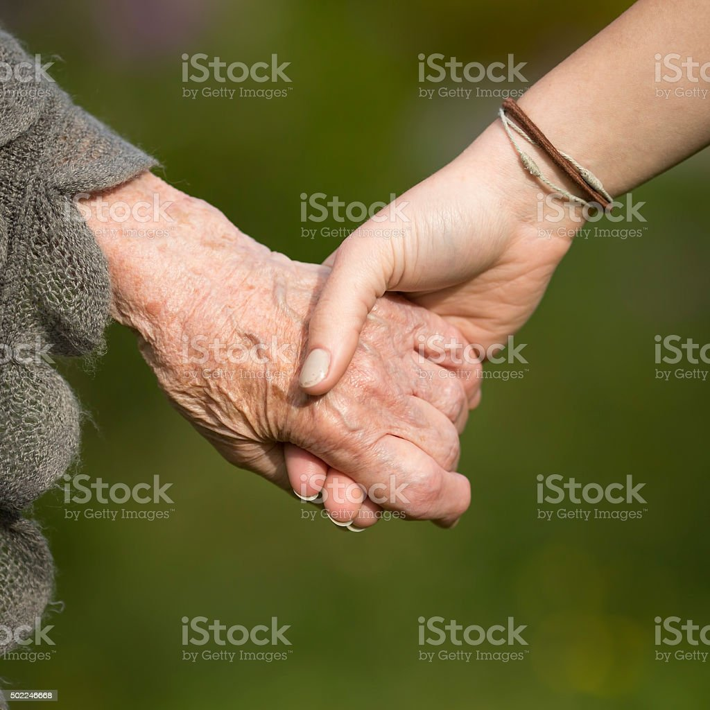 Holding hands of grandmother and child, closeup. stock photo