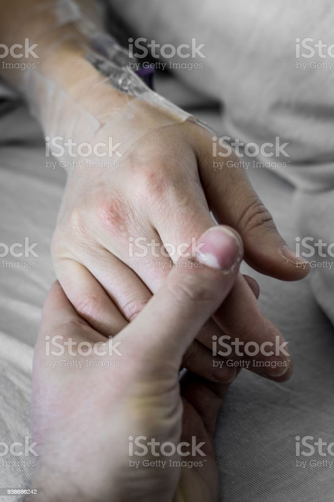 Holding hands on hospital bed stock photo