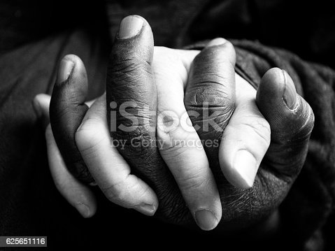 Interracial couple hold hands. Black and white photo.