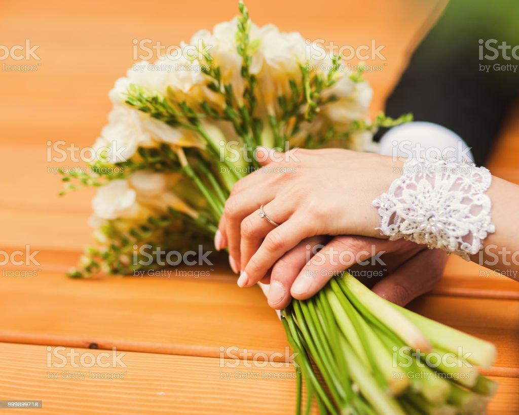 Holding hands young couple. The bridegroom holds a bunch of white roses in her hands. stock photo