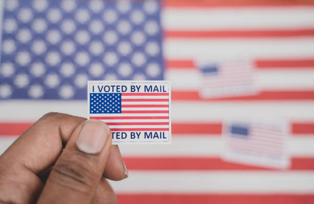 holding i voted my mail sticker in hands with us flag as background - concept of voted through mail during election - ballot stock pictures, royalty-free photos & images