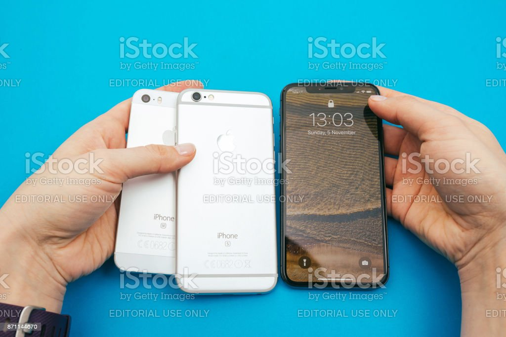 Holding in hands three Apple iPhone mobile phones stock photo