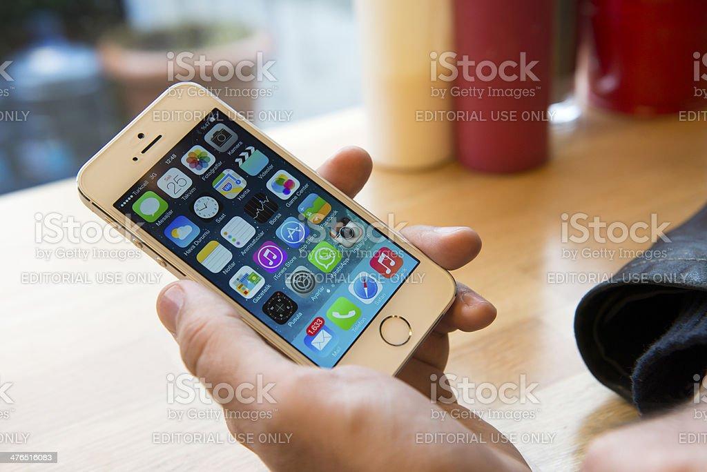 Holding iPhone 5S stock photo