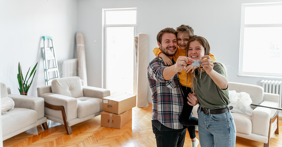 Excited American young family show keys to own home, happy  couple  buying first house together, smiling husband and wife purchase new property. Ownership concept