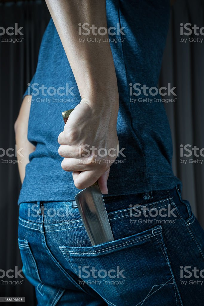 Holding Knife Behind His Back, in dark tone stock photo