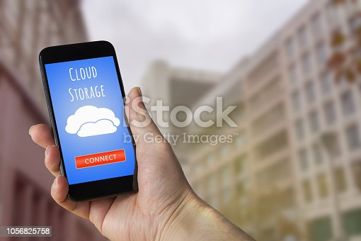 istock Holding mobile phone. Cloud computing concept. 1056825758