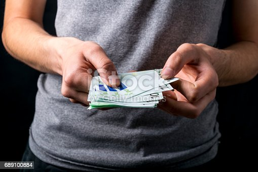 istock holding money of European currency euro. 689100884