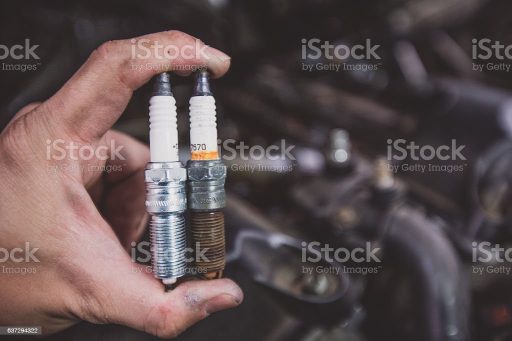 Holding old and new car spark plugs on engine - foto de stock