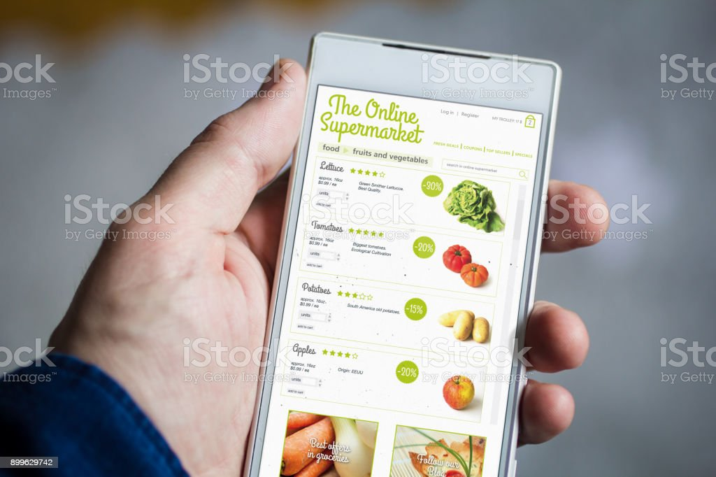 holding online supermarket smartphone stock photo