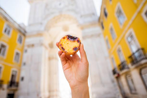 pastel de nata kuchen halten im freien - portugiesische desserts stock-fotos und bilder