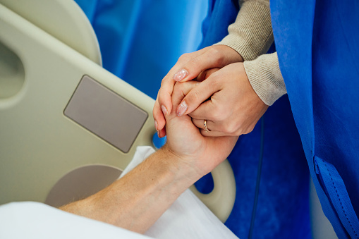 504241549 istock photo Holding patient hands in a hospital. 1219232693