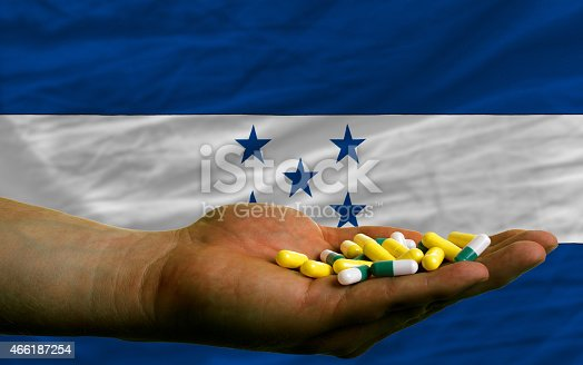 istock holding pills in hand and flag of honduras 466187254