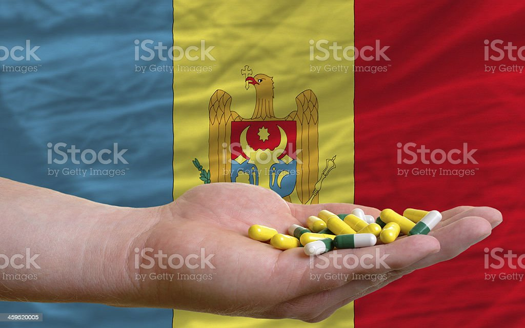 holding pills in hand front of moldova national flag stock photo