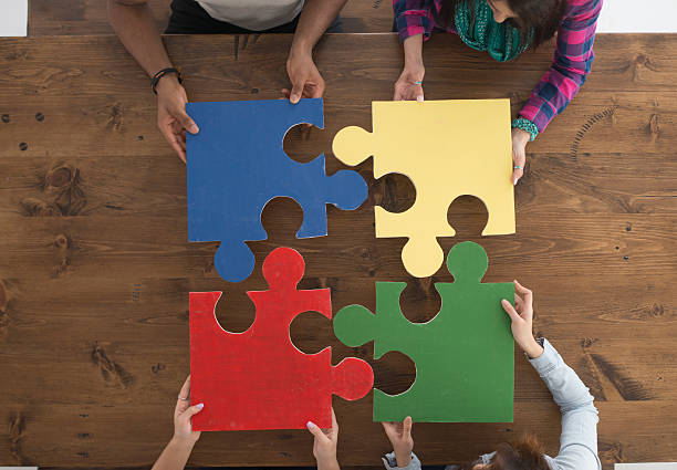 Holding Puzzle Pieces A multi-ethnic group of college age students are putting together large puzzle pieces. four people stock pictures, royalty-free photos & images