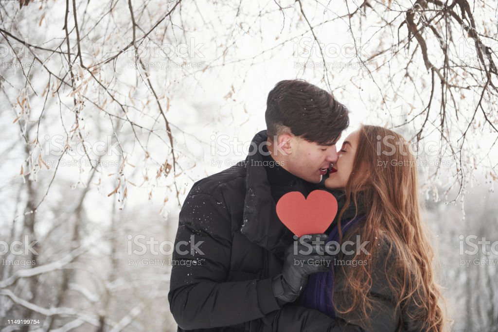 Holding red heart shaped cardboard. Gorgeous young couple have good...