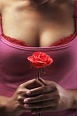 Holding red rose in front of woman body