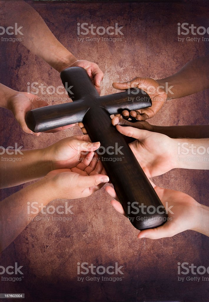 Holding Rugged Cross Together stock photo