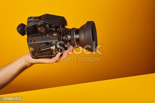 Holding / showing a medium format film camera on yellow / orange colored background