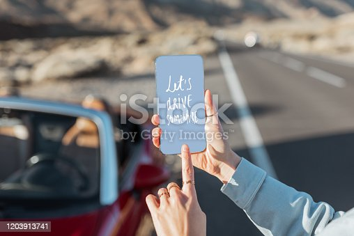 Woman holding smart phone with a text calling to travel on the roadside background, Close-up view