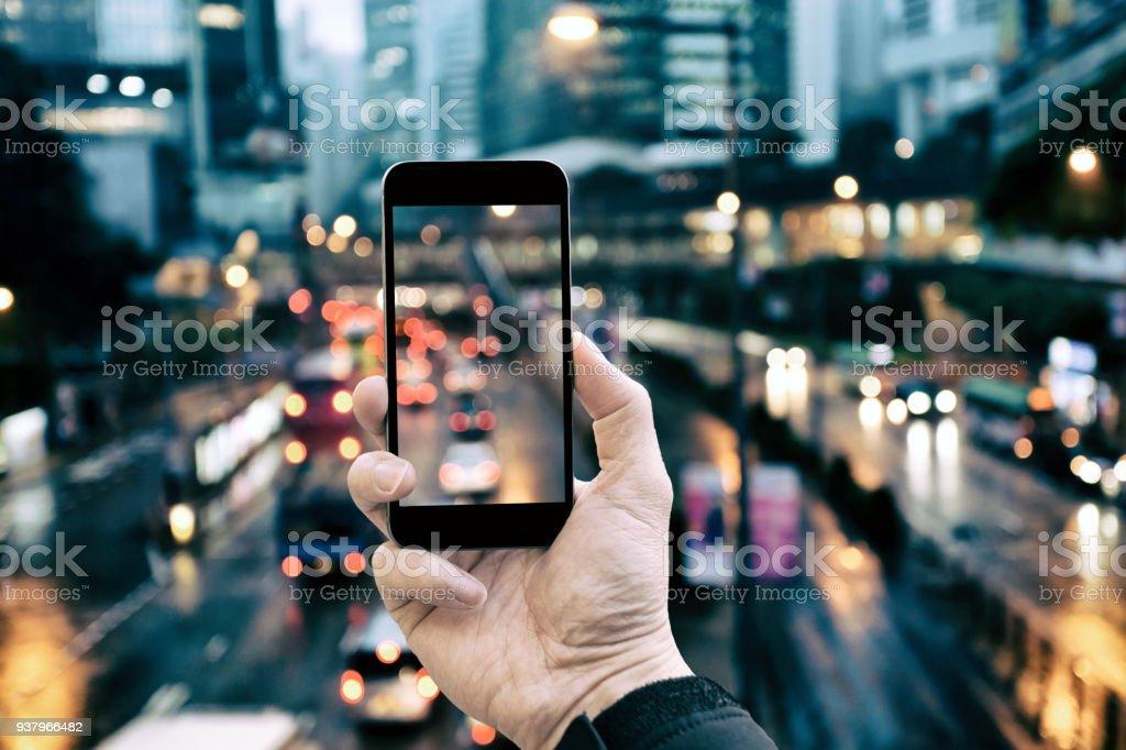 Smartphone hält in der Stadt Nacht – Foto