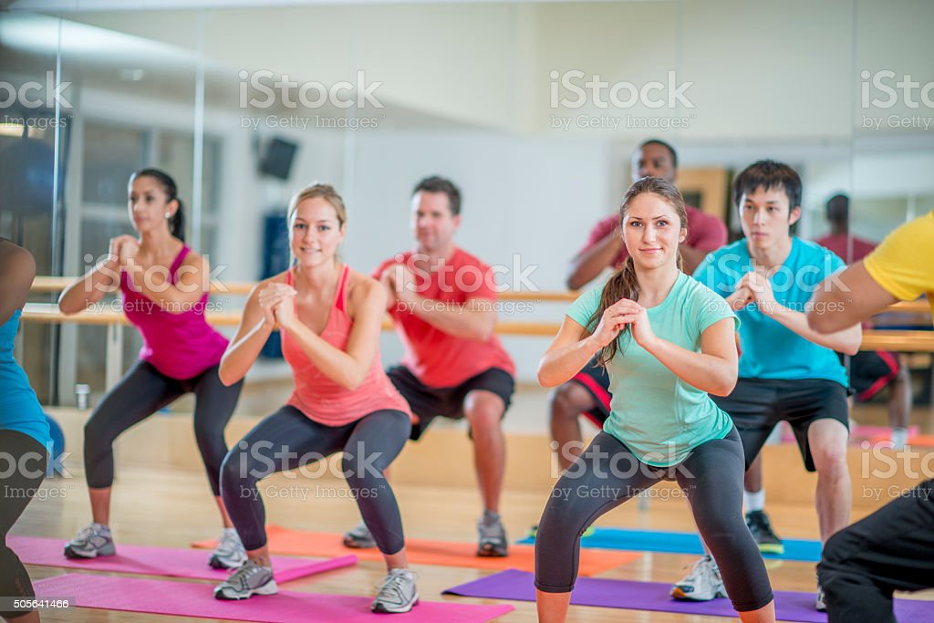 Holding Squats A multi-ethnic group of young adults are working out together in a aerobic fitness class at the gym. They are doing squats with their arms up. Active Lifestyle Stock Photo