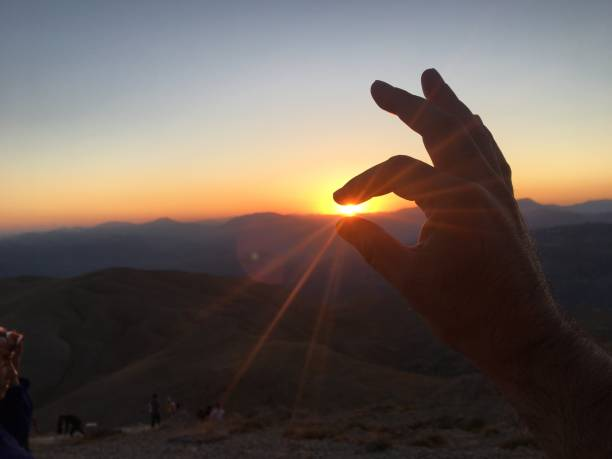 Holding sun with Fingers . Power of perspektive and silhouette. Sunset Sun light shining.Holding sun with Fingers . Power of perspektive and silhouette. Best Sunset  in The world in destination Nemrut mountain . World wonder place . perspektive stock pictures, royalty-free photos & images