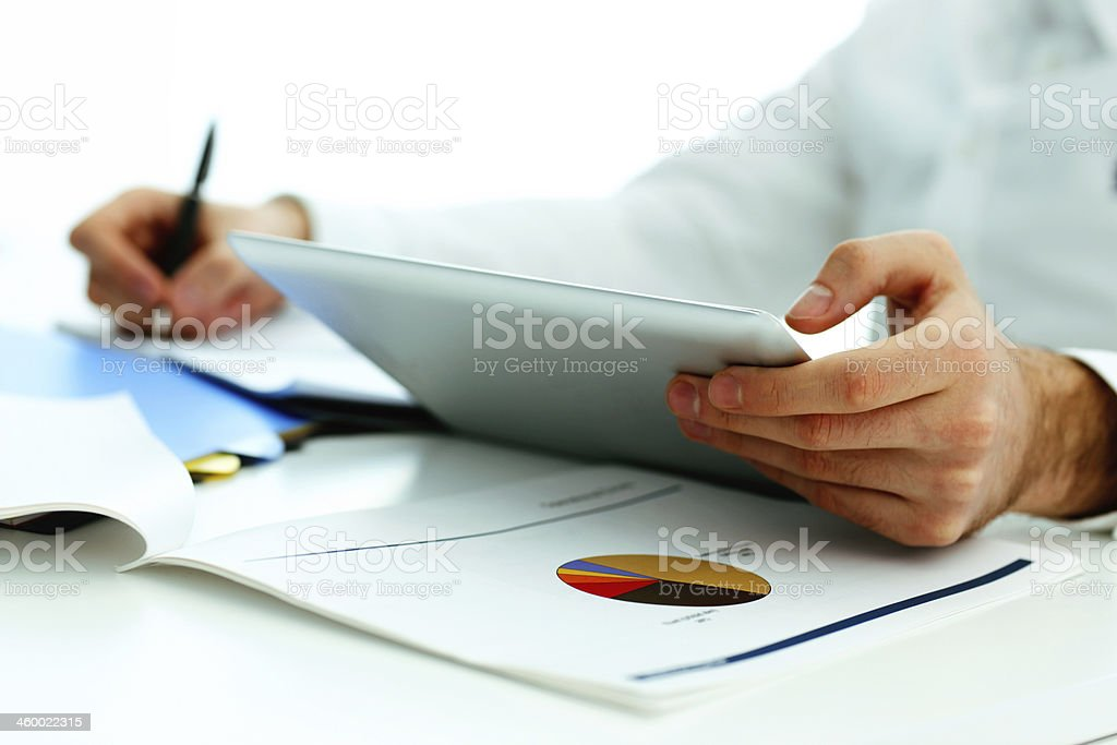 holding tablet computer Closeup image of a man holding tablet computer and writing something down Adult Stock Photo