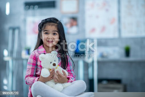 A girl is sitting inside of a hospital room. She is holding a teddy bear, and smiling while waiting for a checkup.