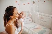 Holding tenderly her newborn baby girl