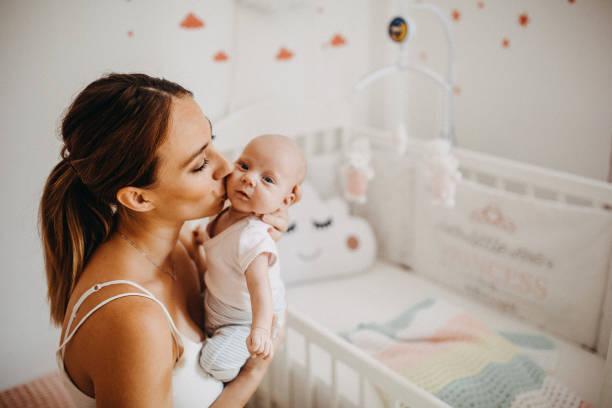 holding tenderly her newborn baby girl - amamentação imagens e fotografias de stock