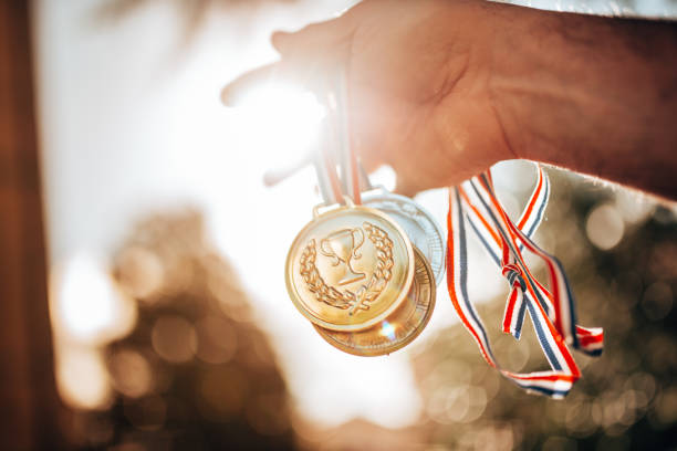 holding the medals for the winning stock photo