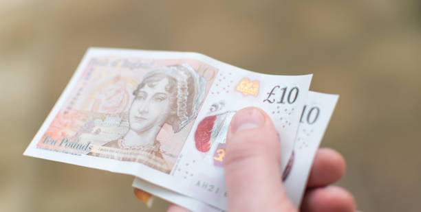 Holding the new for 2017 £10 note UK Currency Holding the new for 2017 £10 note UK Currency with Jane Austen on. ten pound note stock pictures, royalty-free photos & images