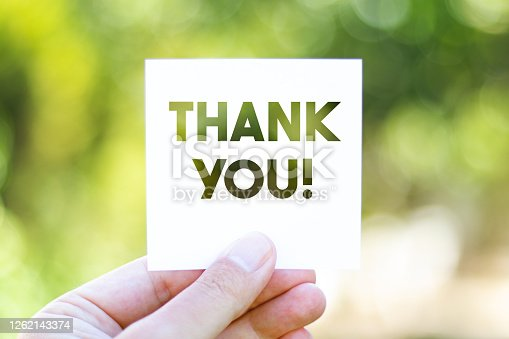 istock Holding the paper with Thank You message in front of a beautiful blur nature background 1262143374