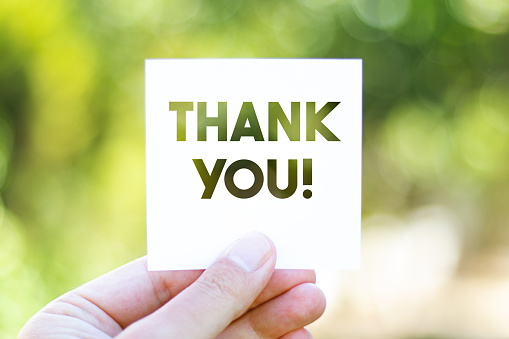 Holding the paper with Thank You message in front of a beautiful blur nature background. Sustainability and environmental concept. Horizontal composition with copy space.