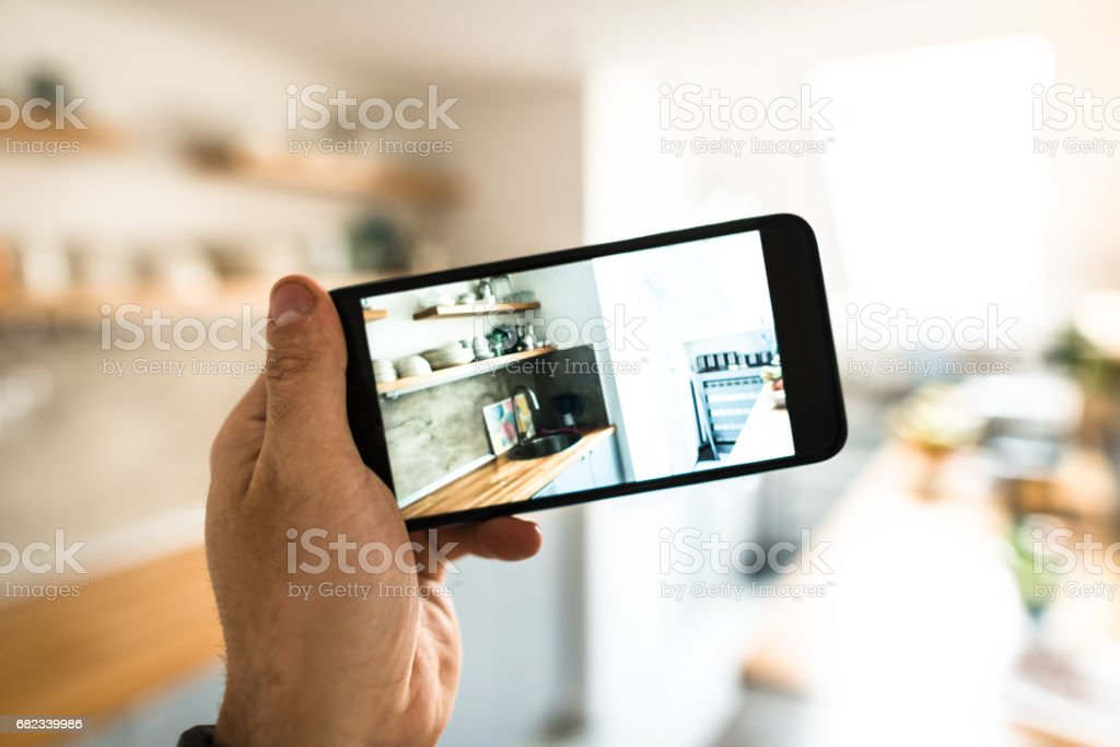 holding the smartphone and photographing the kitchen foto stock royalty-free