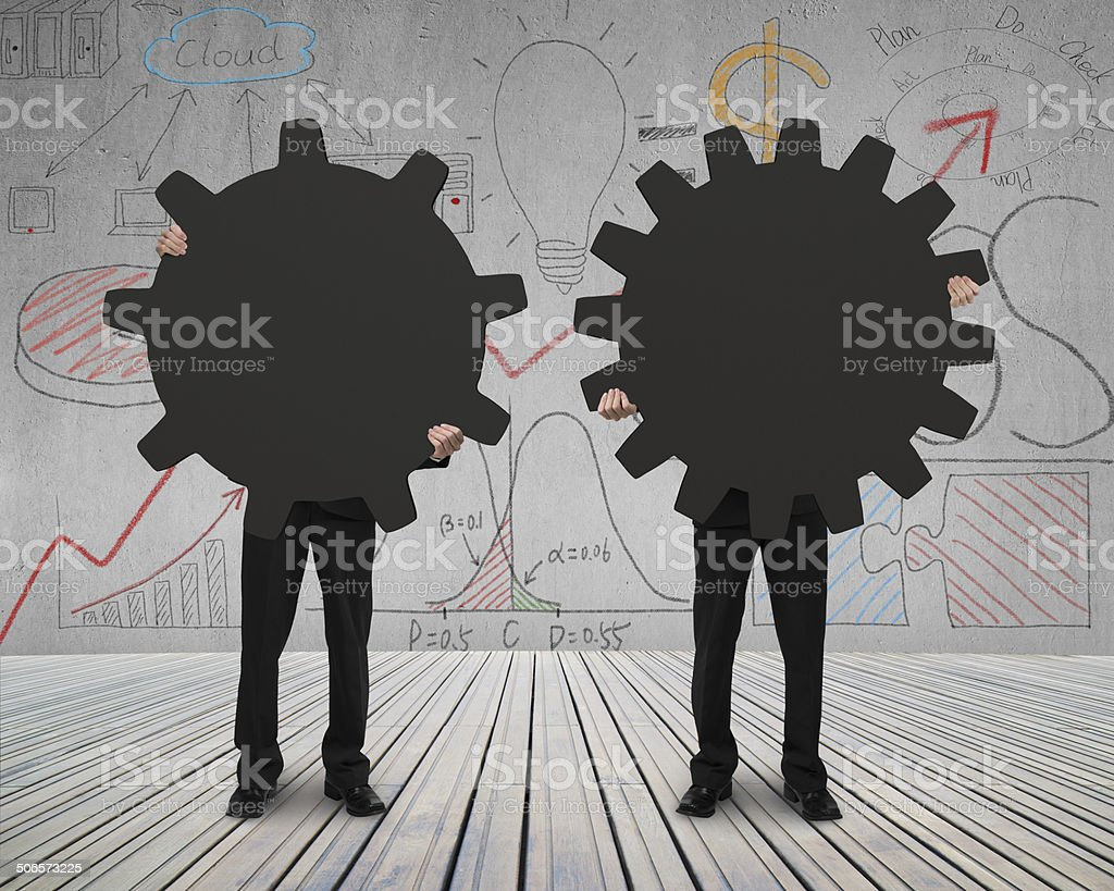 Holding two gears to connect on wooden floor stock photo
