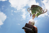 istock Holding up a trophy cup as a winner 692798070