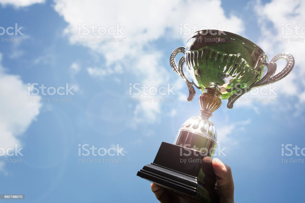 Holding up a trophy cup as a winner stock photo