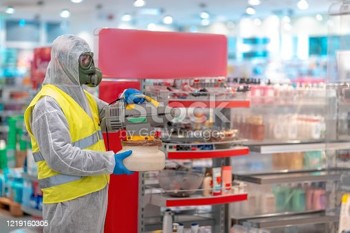 Fully equipped man wearing protective suit and gas mask holding up electrostatic sprayer and disinfecting supermarket shelves in time of virus COVID-19 outbreak